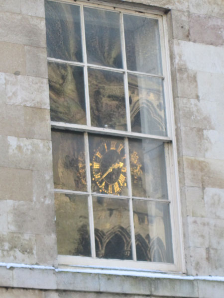 St Mary on the Hill's clock reflected in a Georgian window